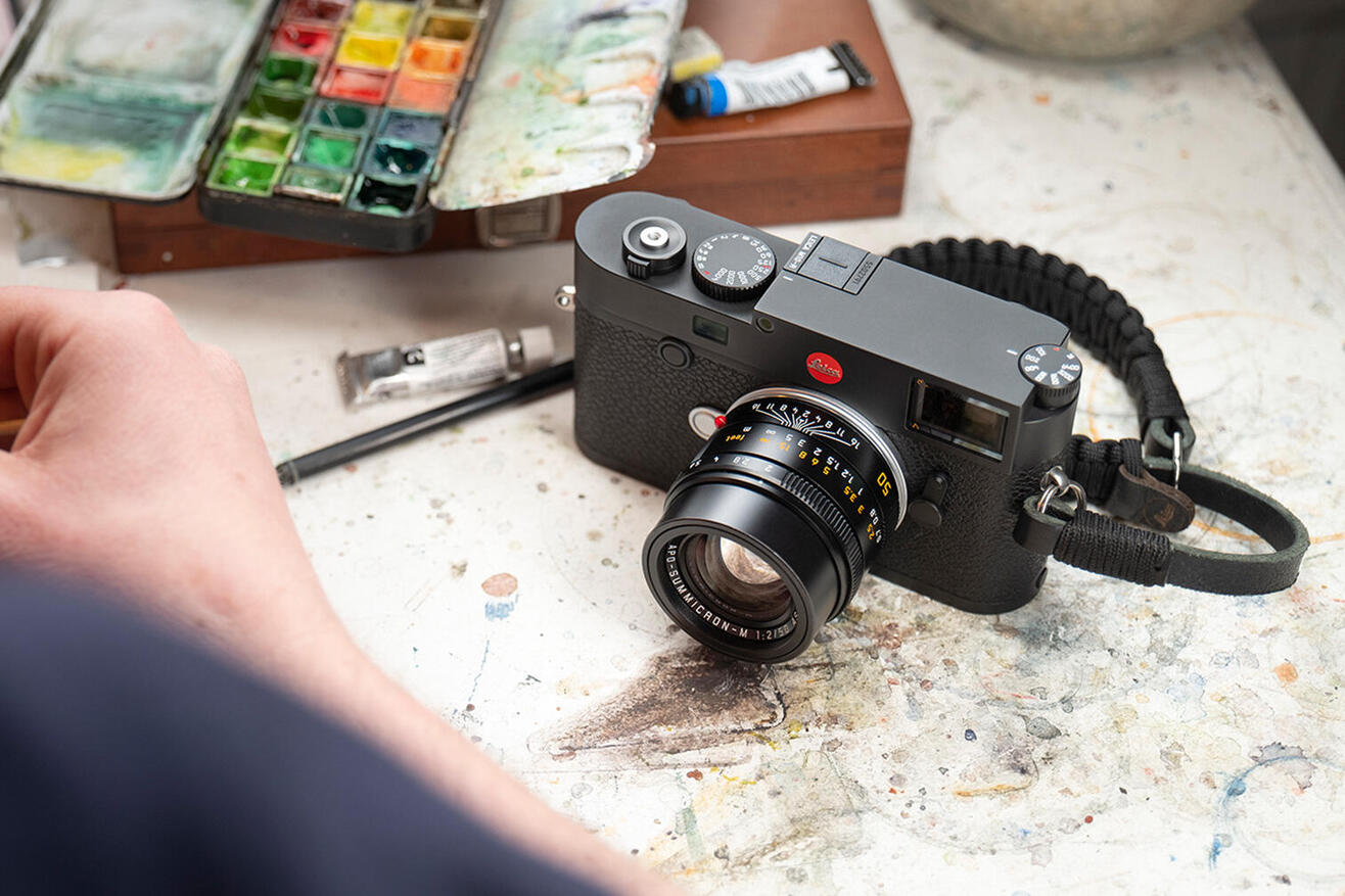 Leica M10-R with paracord wrist strap sitting on table with watercolor palette