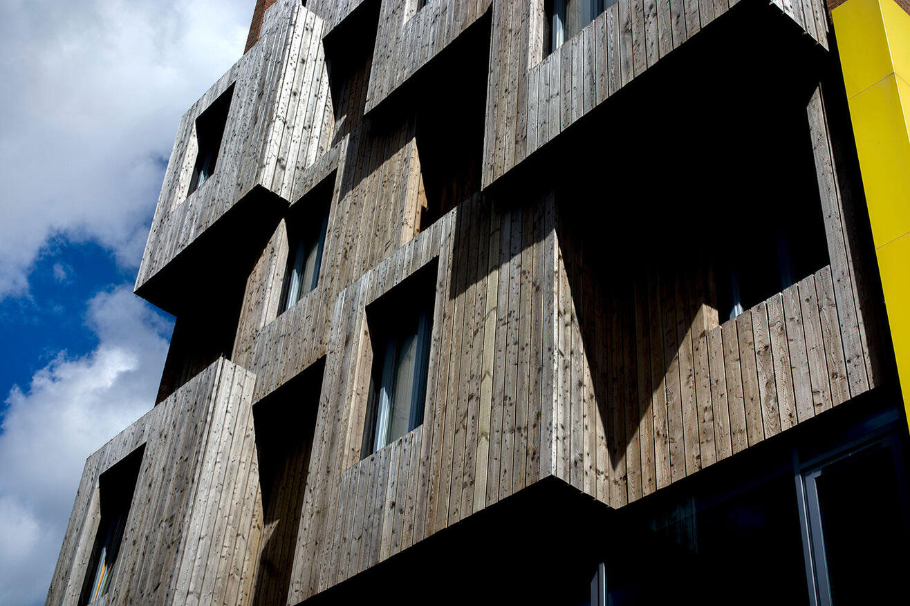 Wooden building with windows and squares of varying heights, causing a lot of shadows