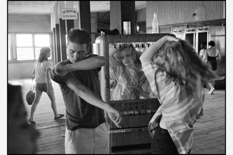 USA. New York City. 1959. Brooklyn Gang. Coney Island. Cathey fixing her hair in a cigarette machine mirror.